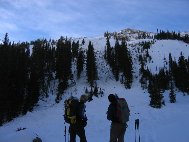 <b>Figure 3:</b> Looking up the path from the toe of the debris pile. The crown wraps from just left of the left hand person around to the right to a point above the ski poles to the right of the person on the right (<a href=javascript:void(0); onClick=win=window.open('http://avalanche.state.co.us/caic/media/full/acc_225_307.jpg','caic_media','resizable=1,height=820,width=840,scrollbars=yes');win.focus();return false;>see full sized image</a>)