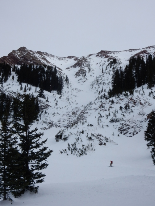 <b>Figure 8:</b> Looking up at the terrain feature and avalanche path.  Skier 2 and the debris pile ended about 100 meters up slope from the skier shown in this photo. (<a href=javascript:void(0); onClick=win=window.open('http://avalanche.state.co.us/caic/media/full/acc_632_15807.jpg','caic_media','resizable=1,height=820,width=840,scrollbars=yes');win.focus();return false;>see full sized image</a>)