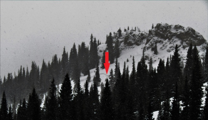 <b>Figure 2:</b> A distant image of the slope that avalanched. The red arrow points to the face of the crown.The skiers entered the slope to the left of the arrow, below the large rock outcrop. (<a href=javascript:void(0); onClick=win=window.open('https://avalanche.state.co.us/caic/media/full/acc_693_23705.jpg','caic_media','resizable=1,height=820,width=840,scrollbars=yes');win.focus();return false;>see full sized image</a>)