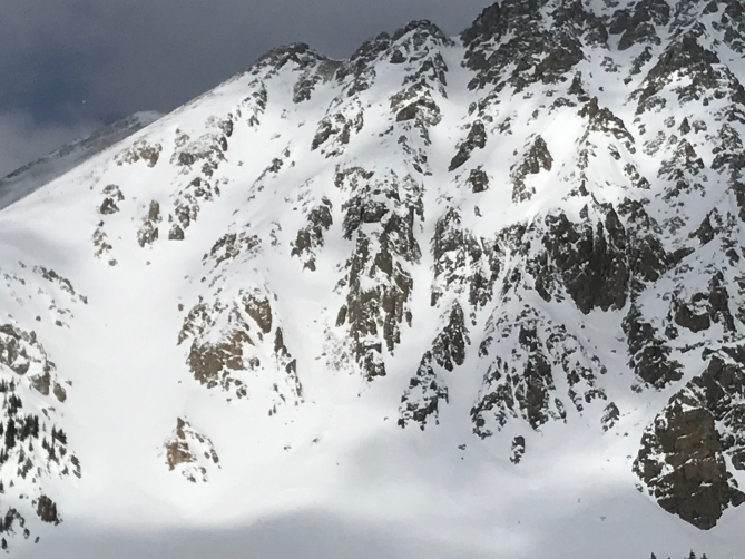 <b>Figure 1:</b> On March 23, 2019 a group of 6 was bootpacking up the thin, confined, couloir in the middle of this image. They were about 3/4 of the way to the ridge when they triggered an avalanche. The avalanche broke 18 inches deep and propagated the whole width of the couloir. Four of the six were caught, two were swept about 600 feet downhill and were deposited on the surface just above where the mouth of the couloir opens onto the apron below. Five of the group sustained minor injuries. Nobody was buried. (<a href=javascript:void(0); onClick=win=window.open('https://avalanche.state.co.us/caic/media/full/acc_717_26086.jpg','caic_media','resizable=1,height=820,width=840,scrollbars=yes');win.focus();return false;>see full sized image</a>)