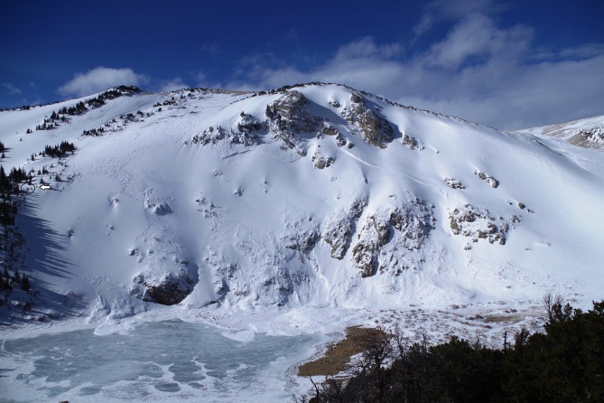 <b>Figure 8:</b> Picture of avalanche area from Fox Peak to the east of St Mary's Lake. Small black oval and white arrow point to CAIC doing a snowpit profile (<a href=javascript:void(0); onClick=win=window.open('https://avalanche.state.co.us/caic/media/full/obs_38681_11352.jpg','caic_media','resizable=1,height=820,width=840,scrollbars=yes');win.focus();return false;>see full sized image</a>)