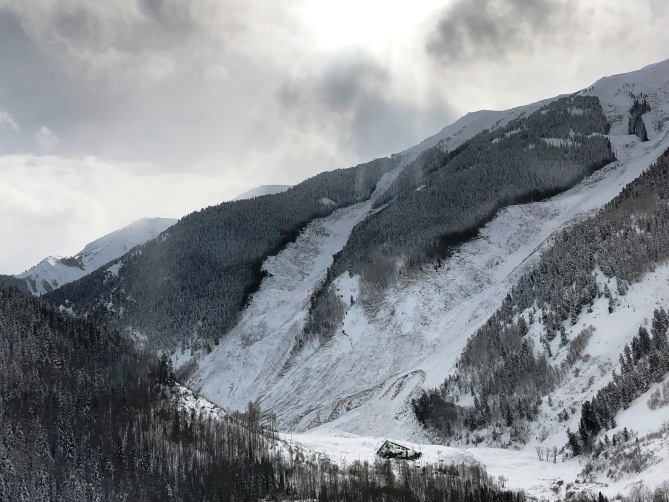 <b>Figure 2:</b> Historic-sized avalanche off Highlands Ridge. The house in the bottom of the image is protected by a defensive wedge but still suffered damage like a destroyed chimney shattered, windows, and maybe more.  March 9, 2019 Image courtesy of Telluride Helitrax. (<a href=javascript:void(0); onClick=win=window.open('https://avalanche.state.co.us/caic/media/full/obs_55413_25368.jpeg','caic_media','resizable=1,height=820,width=840,scrollbars=yes');win.focus();return false;>see full sized image</a>)