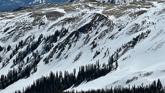 Large cornices and small loose wet slides out of rocky areas above treeline in the Northern Mountains near Uneva Peak on a north facing slope. April 30, 2021.